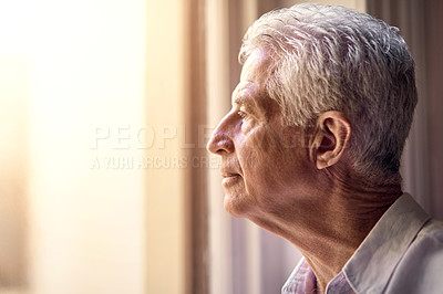 Buy stock photo Shot of a thoughtful senior man looking out of the window at home