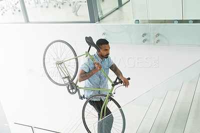 Buy stock photo Shot of a young designer carrying his bicycle up a staircase in an office