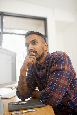 Buy stock photo Shot of a young designer contemplating a new project at his desk in the office