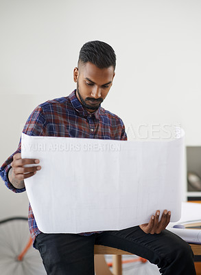 Buy stock photo Shot of a creative young architect studying a roll of blueprints in his office