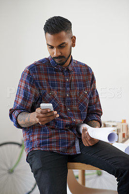 Buy stock photo Shot of a creative young architect using his smartphone while holding a roll of blueprints in his office