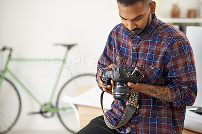 Buy stock photo Shot of a focussed young photographer holding his camera while leaning on his desk in the office