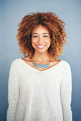 Buy stock photo Studio portrait of an attractive and happy young woman posing against a grey background