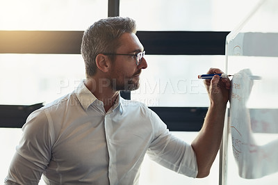 Buy stock photo Cropped shot of a mature businessman working on a whiteboard in his office