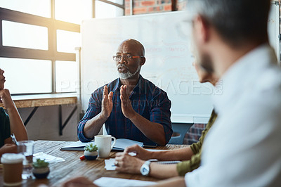 Buy stock photo Cropped shot of a group of business colleagues in the office having a meeting and discussing plans for the future