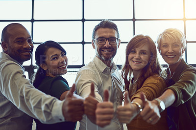 Buy stock photo Portrait of a team of colleagues giving a thumbs up in a modern office