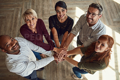 Buy stock photo High angle portrait of a group of colleagues joining their hands in solidarity at work