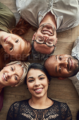 Buy stock photo High angle portrait of a group of colleagues lying together in a circle on the floor at work