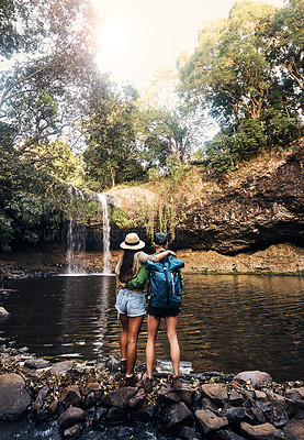 Buy stock photo Rearview shot of two young female friends holding each other looking at a waterfall in the forest