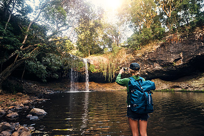Buy stock photo Rearview shot of a young woman capturing a waterfall with her smartphone outdoors