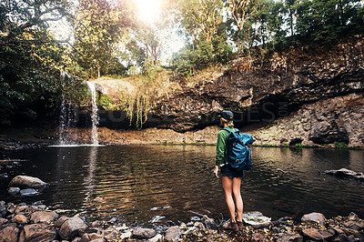 Buy stock photo Shot of a young woman looking at a waterfall outdoors in the forest