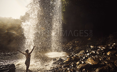 Buy stock photo Rearview shot of a young woman arms raised getting wet underneath a waterfall in nature