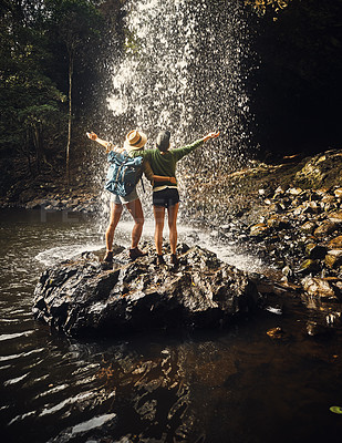Buy stock photo Rearview shot of two female best friends arms raised by a waterfall enjoying a day in nature