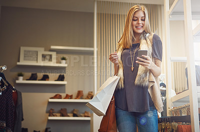 Buy stock photo Shot of a young woman using her cellphone while out shopping