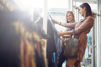 Buy stock photo Shot of a young woman holding up an item that she picked out in a clothing store