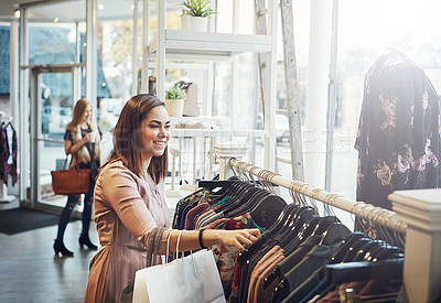 Buy stock photo Shot of a young woman shopping at a clothing store