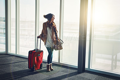 Buy stock photo Shot of a young woman standing in an airport with her luggage and staring outside