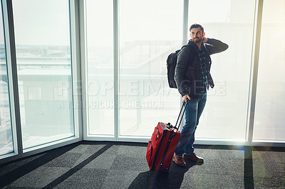 Buy stock photo Shot of a young man standing in an airport with his luggage looking confused and smiling