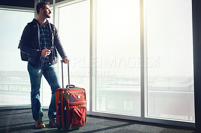 Buy stock photo Shot of a young man standing in an airport with luggage and looking outside while holding his cellphone