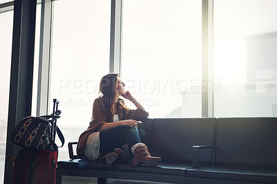 Buy stock photo Shot of a young woman sitting inside of an airport with her luggage looking outside with her cellphone in her hand