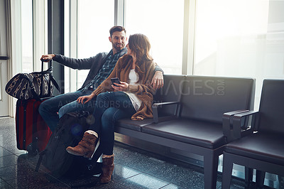 Buy stock photo Shot of a young couple seated in an airport with their luggage looking at one another and smiling