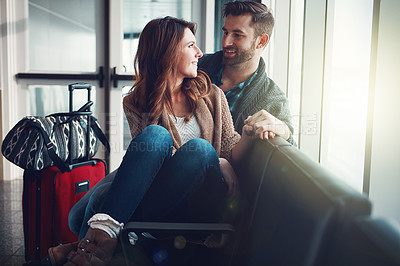 Buy stock photo Shot of a young couple sitting in an airport with their luggage and holding one another and looking at each other
