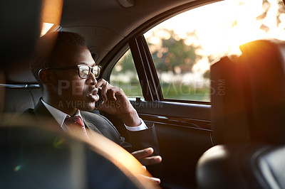 Buy stock photo Shot of a focussed young businessman making a call on his smartphone while traveling in the back seat of a car