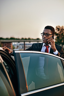 Buy stock photo Shot of a focussed young businessman making a call on his smartphone while standing next to his parked car
