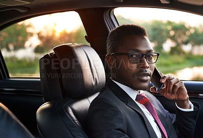 Buy stock photo Portrait of a focussed young businessman using his cellphone while sitting in a parked car