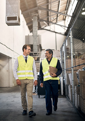 Buy stock photo Shot of two colleagues working together in a factory
