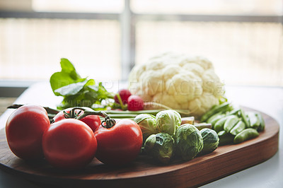 Buy stock photo Shot of a variety of fresh produce on a wooden chopping board