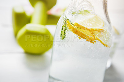 Buy stock photo Shot of a jug of water and dumbbells on a table