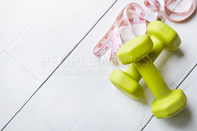 Buy stock photo Shot of dumbbells and a measuring tape on a table