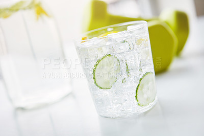Buy stock photo Shot of a glass of water with slices of lemon and cucumber in