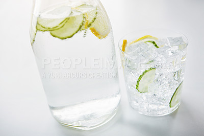 Buy stock photo Shot of a jug and glass of water with slices of lemon and cucumber in