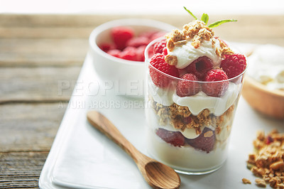 Buy stock photo Shot of of granola, yoghurt and berries in a glass and on a plate