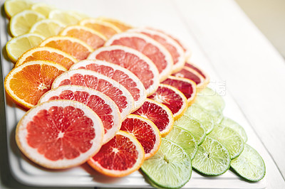 Buy stock photo Shot of a variety of citrus fruits cut into slices on a plate