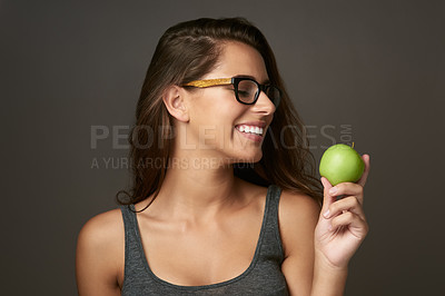 Buy stock photo Studio shot of a beautiful young woman looking at an apple against a brown background
