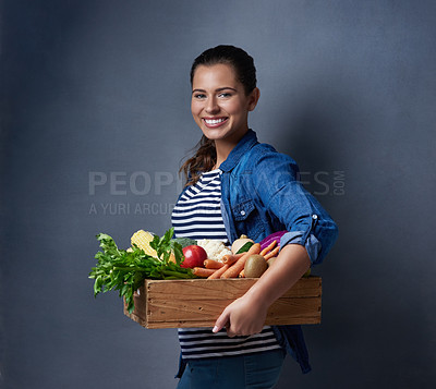Buy stock photo Studio shot of a beautiful young woman holding a wooden crate full of vegetables and fruit against a blue background
