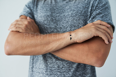 Buy stock photo Studio shot of an unrecognizable man with a semi colon tattoo standing with his arms folded
