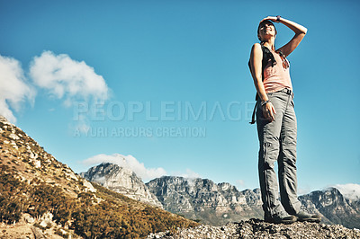 Buy stock photo Shot of a young woman admiring the view while out on a hike through the mountains