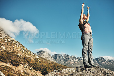 Buy stock photo Shot of a young woman celebrating while out on a hike through the mountains
