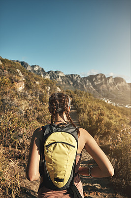 Buy stock photo Rear view shot of a young woman out on a hike through the mountains