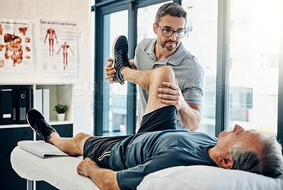 Buy stock photo Shot of a friendly physiotherapist treating his mature patient in a rehabilitation center