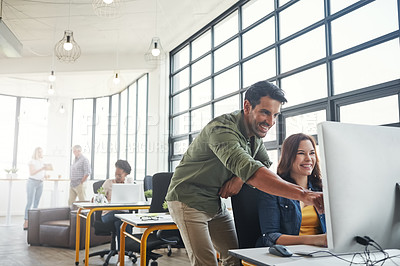 Buy stock photo Shot of a male designer assisting his colleague at her desk
