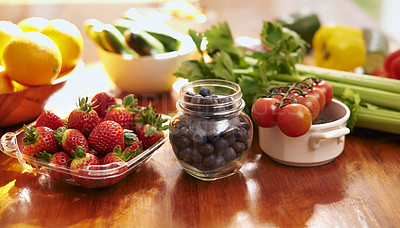 Buy stock photo Shot of a variety of fresh fruit and vegetables on a kitchen counter