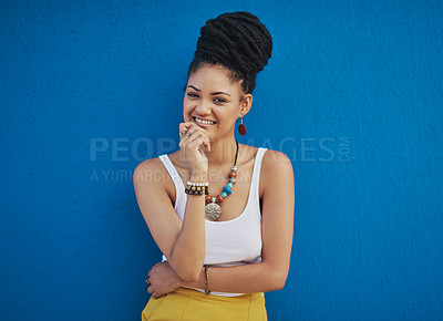Buy stock photo Portrait of an attractive and trendy young woman posing against a blue background