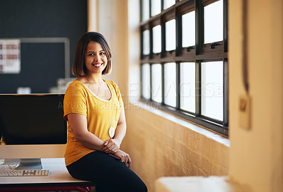 Buy stock photo Cropped portrait of an attractive young businessman leaning on a desk in her office