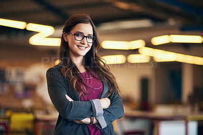 Buy stock photo Cropped portrait of an attractive young businesswoman standing with her arms folded in the office