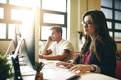 Buy stock photo Cropped shot of two young colleagues working at their desk in the office